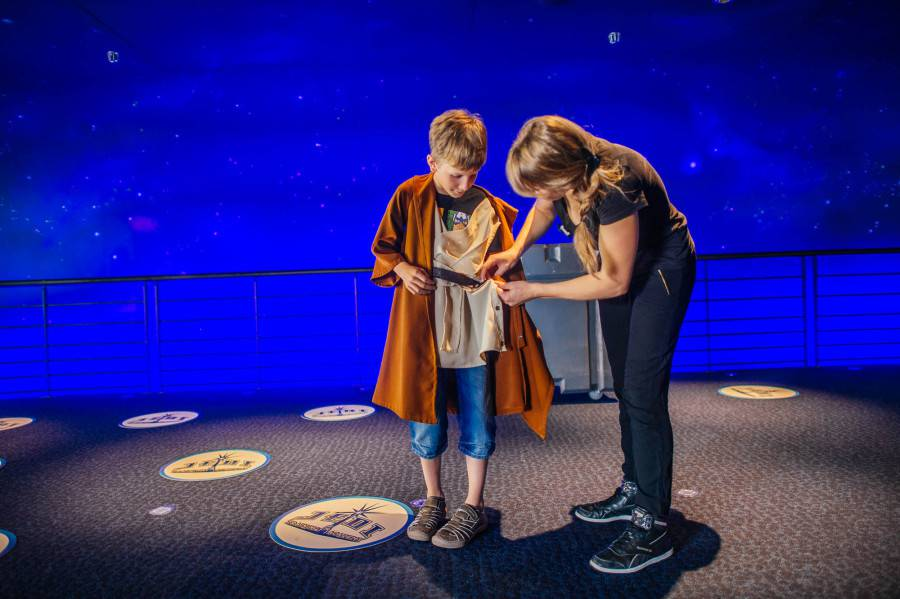 A Padawan is being fit in a Jedi Tunic by a Cast Member.